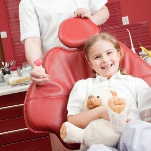 A little girl smiling in a pediatric dental chair