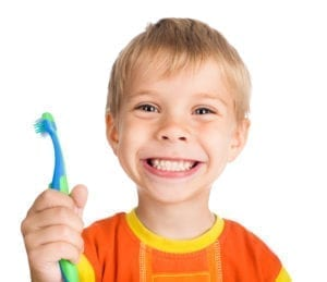 Boy smiling holding toothbrush