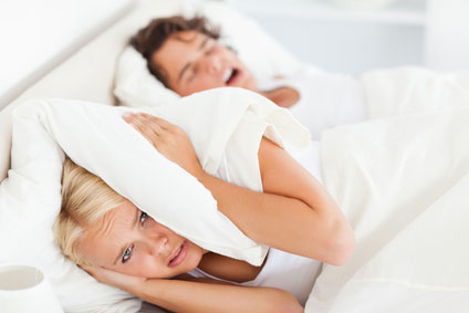 Woman covering her ears trying to block out her husband snoring
