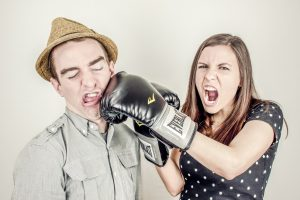 Woman with a boxing glove punching someone
